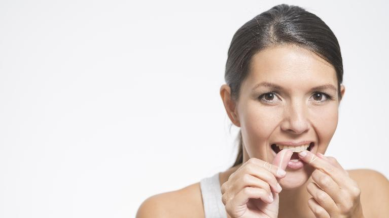 west chester oh dentist | woman flossing